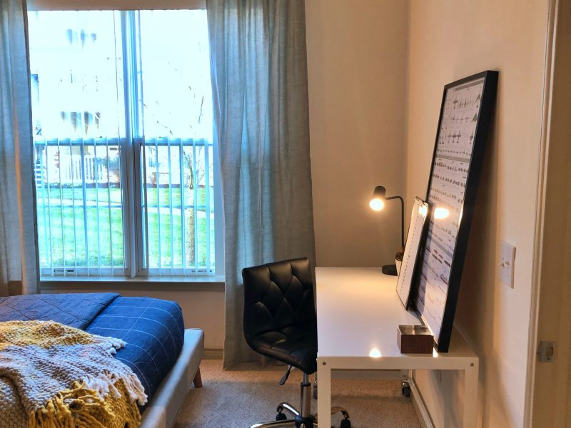 This image shows the Premium Apartment Feature, particularly the bedroom area showcasing the light tone color wall, elegant fabrics, and an overlooking view outside that was ideal for a comfy pleasure.