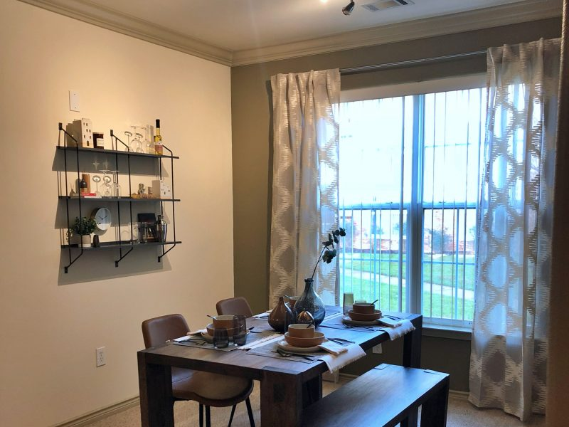 This image shows the Premium Apartment Feature, particularly the dining room area featuring minimalist decor, elegant furniture, and a wooden dining table that was suitable for a spacious area.