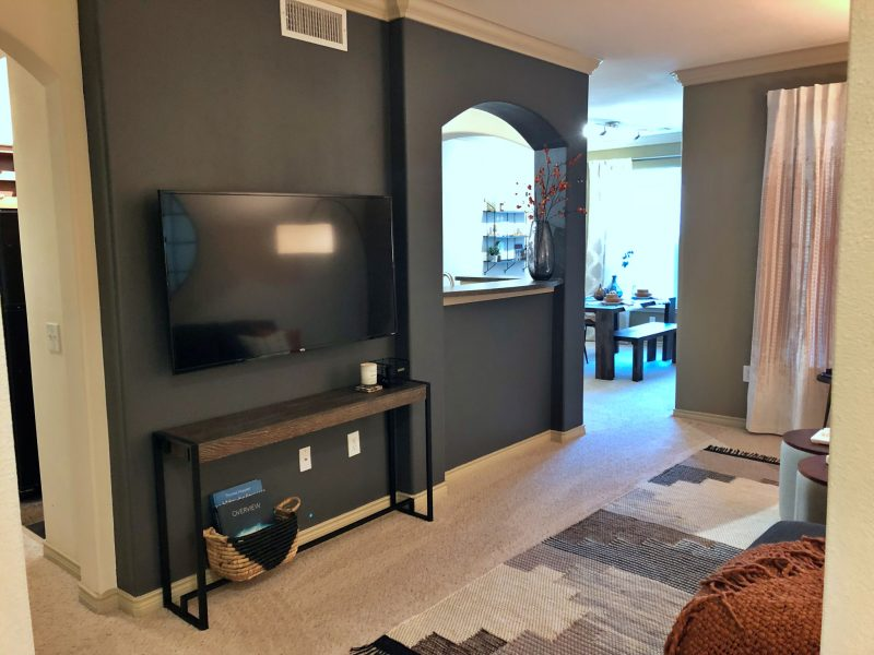 This image shows the living room area featuring a dark wall color, elegant furniture, and minimal wall decors that were suitable for a spacious area. The living room was also accessible to the dining area.
