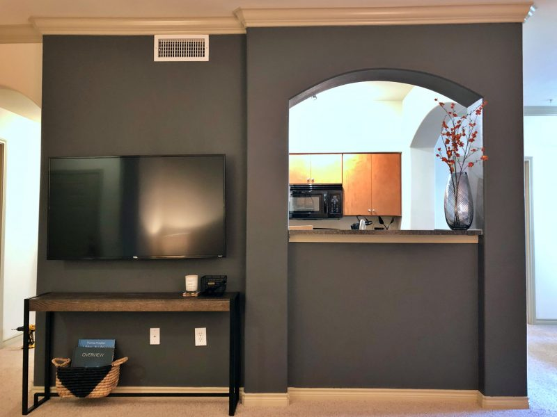This image shows the living room area featuring a flat-screen TV and a direct access to the kitchen area.
