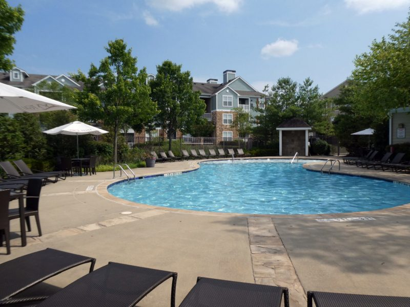 This image shows the resort-style outdoor swimming pool that is offering comfortable beds nearby the pool.